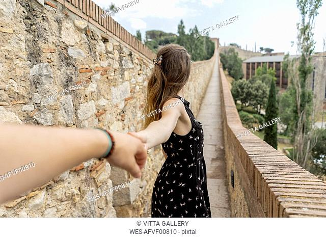 Spain, Girona, woman holding man's hand walking along stone wall