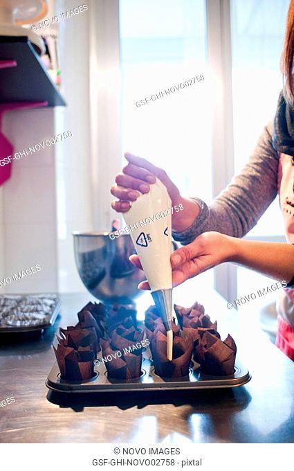 Woman Filling Cupcake Molds