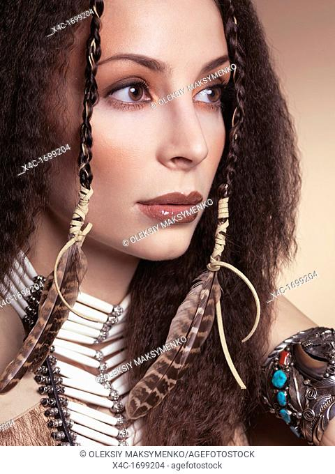 Artistic beauty portrait of a beautiful woman wearing aboriginal native accessories and feathers in her hair
