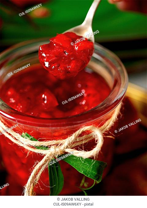 Jar of homemade redcurrant jam and spoon