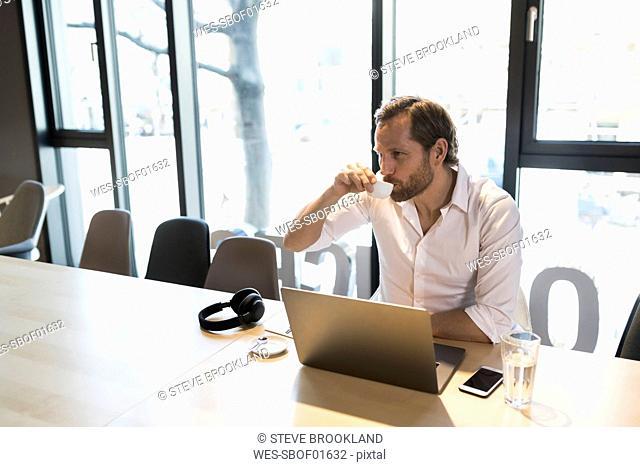 Casual entrepreneur having an espresso break in modern office space
