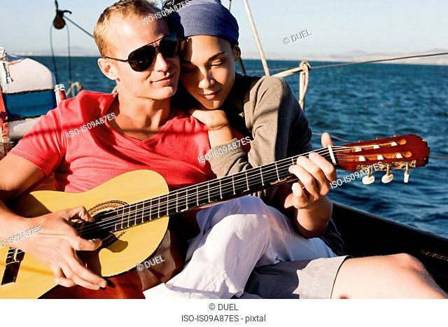 Couple on yacht, man playing guitar