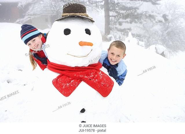 Portrait of boy and girl with snowman