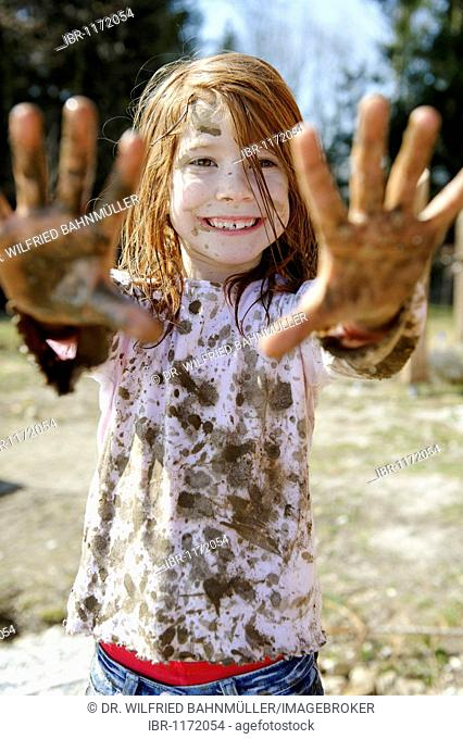 Child totally covered in mud, dirty, wild, untypical girl