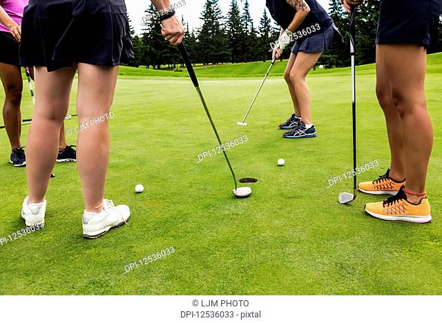 A foursome of female golfers on a putting green taking turns putting using the best ball in a Texas Scramble during a tournament; Edmonton, Alberta, Canada