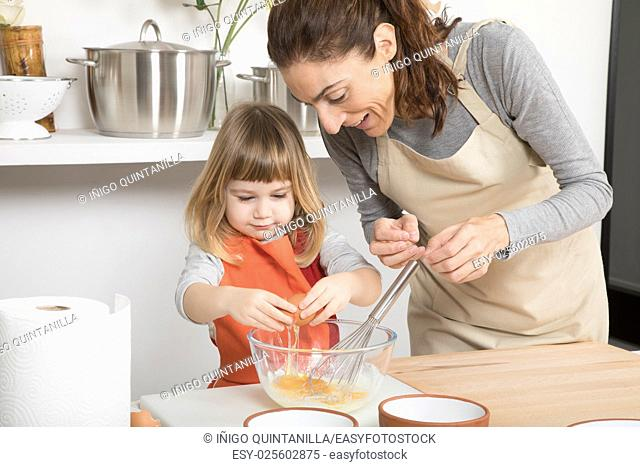 three years old child with orange apron and woman mother with beige, in teamwork, making and cooking a sponge cake at kitchen home