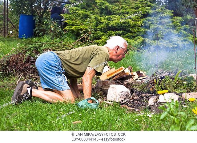 Senior man trying to make a bonfire in the garden