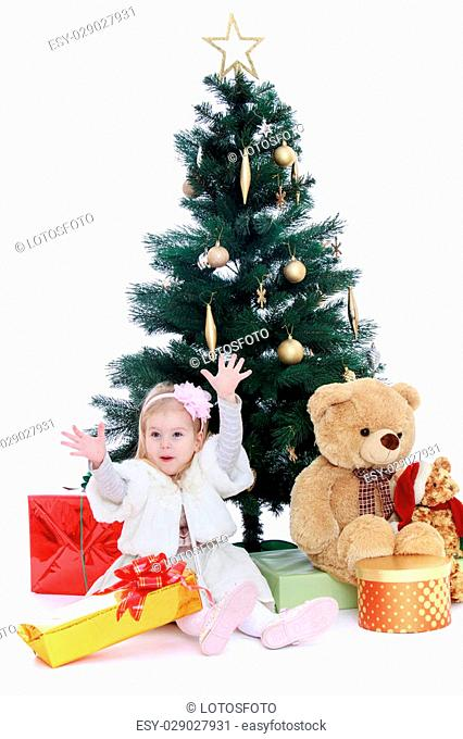 965ba370ce6f Happy little girl in fancy dress sitting around the Christmas tree-Isolated  on white background