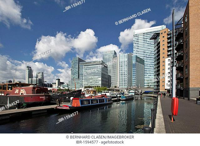 House boat in the port, office buildings and residential houses in Canary Wharf, the new financial district of London in the Docklands