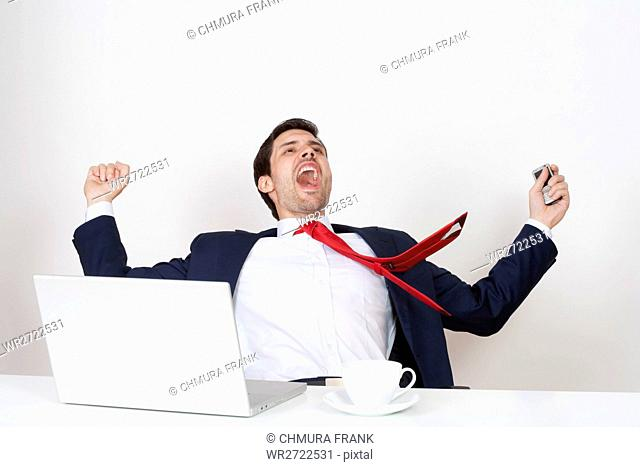 young business executive in suit cheering behind desk