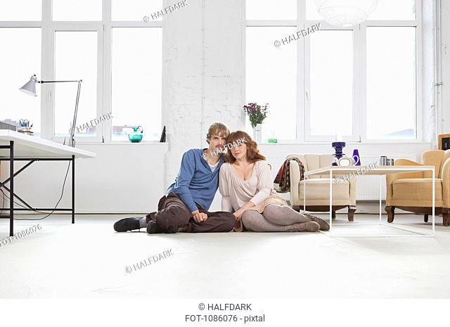 A young couple sitting side by side on the floor