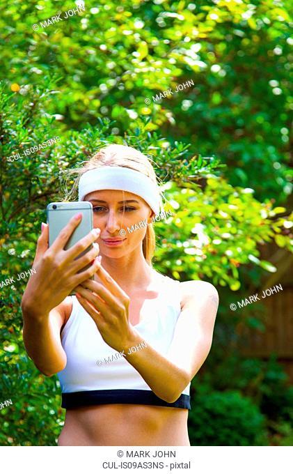 Woman wearing sports top taking selfie in garden