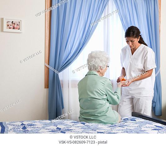 USA, Illinois, Metamora, Nurse giving pills to senior woman sitting on bed