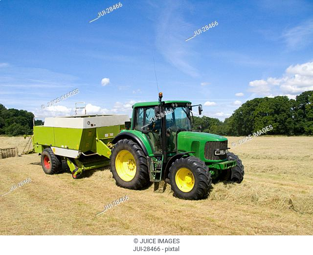 Tractor bailing hay in farm field under blue sky