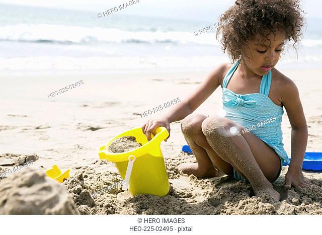 Girl in bathing suit making sandcastle on beach