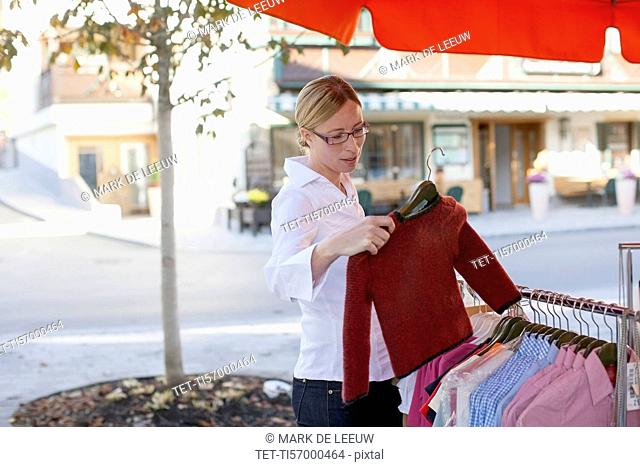 Woman taking sweater from clothes rack