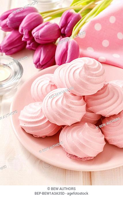 Pink meringues on cake stand. Party dessert