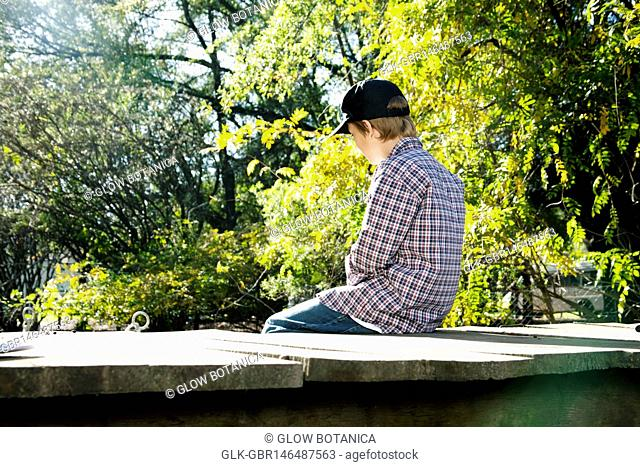 Boy sitting on a footbridge