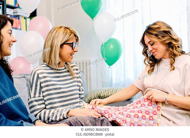 Pregnant woman and friends on sofa looking at baby blanket