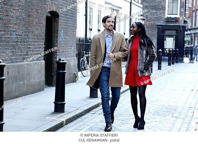 Couple walking along street, arm in arm, smiling