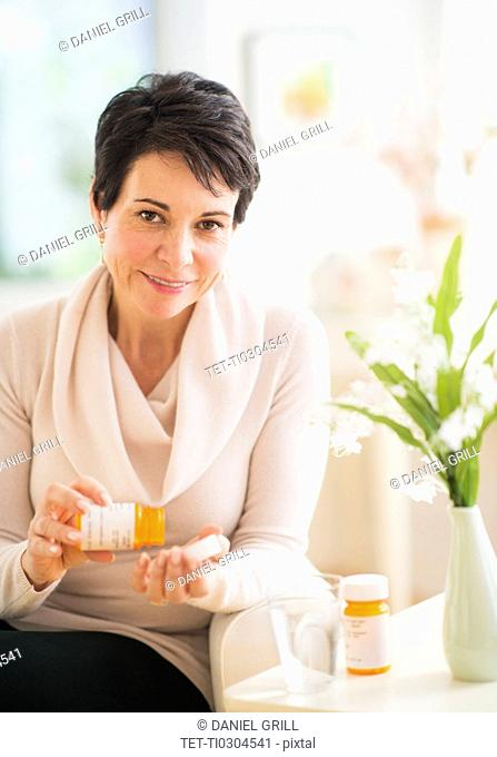 Portrait of mature woman taking pills