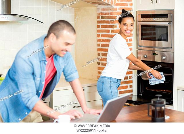 Young man using laptop and her girlfriend baking