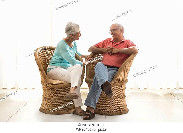 Senior couple sitting on wicker chair and talking