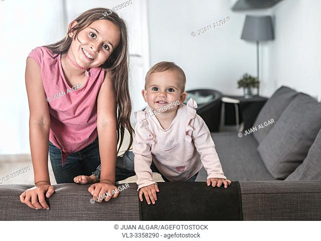 Two girls smiling on the couch at home