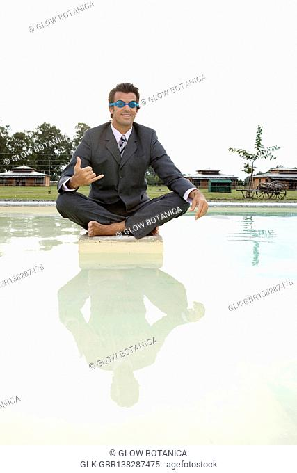Businessman sitting on a stone in a pond