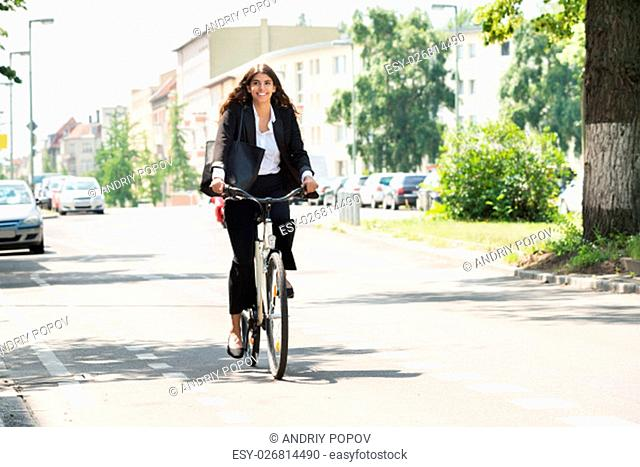 Smiling Young Businesswoman Riding Bicycle On Street