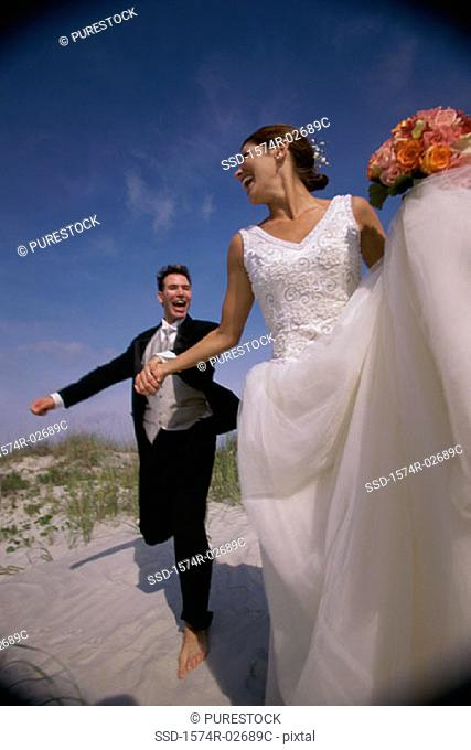 Newlywed couple running on sand