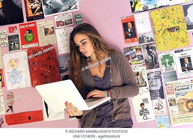 Teen girl in her bedroom with laptop computer