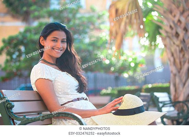 Closeup portrait young beautiful happy woman in white dress, sitting on bench, isolated green palm trees, nature background