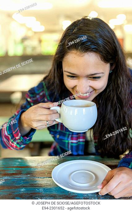 19 year old brunette woman holding a coffee cup in a restaurant