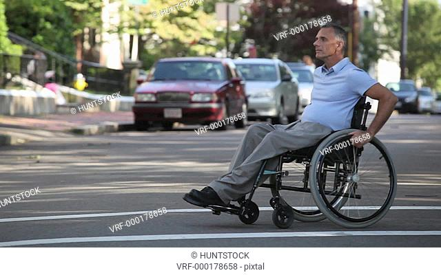 Man with spinal cord injury in a wheelchair crossing street at accessible access