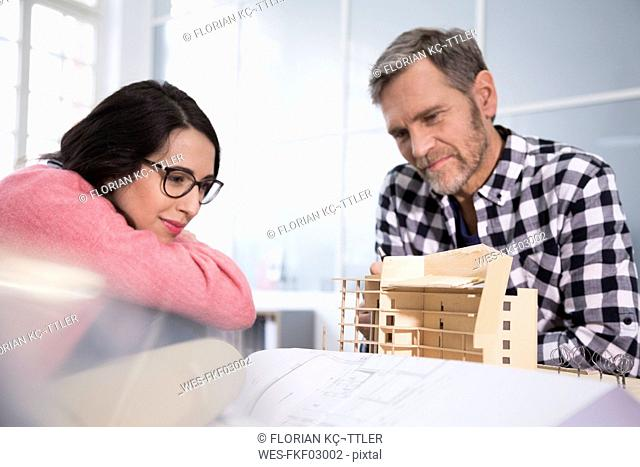Smiling colleagues looking at architectural model in office