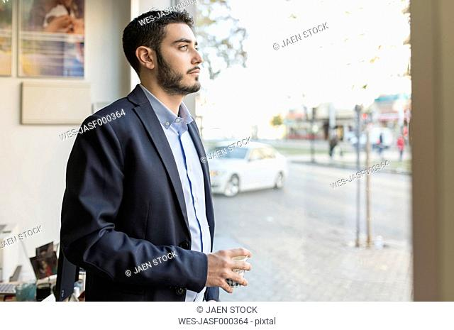 Serious young businessman looking out of window