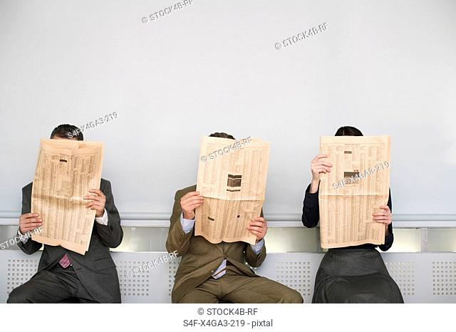 Three businesspeople reading newspaper