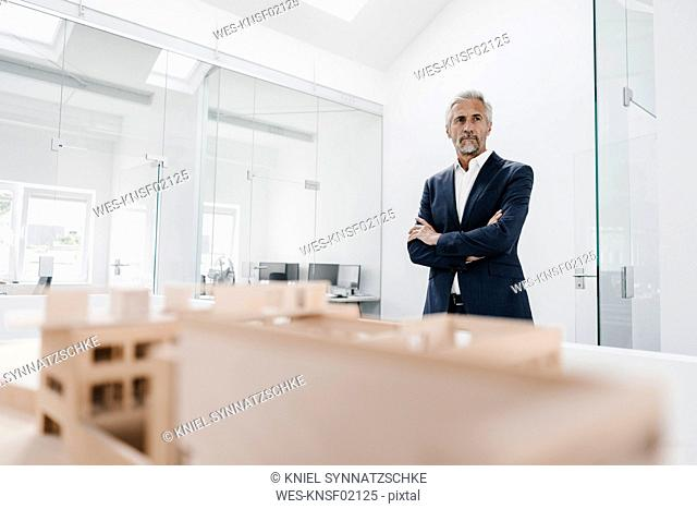 Mature businessman with architectural model in office