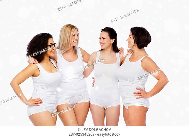 friendship, beauty, body positive and people concept - group of happy women different in white underwear over snow