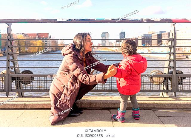 Mother and daughter by river, Berlin, Germany