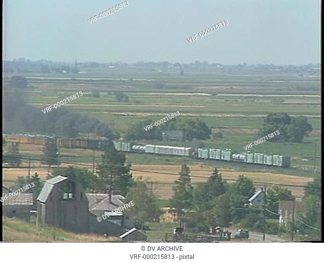 Long shot of a steam train passing through the countryside