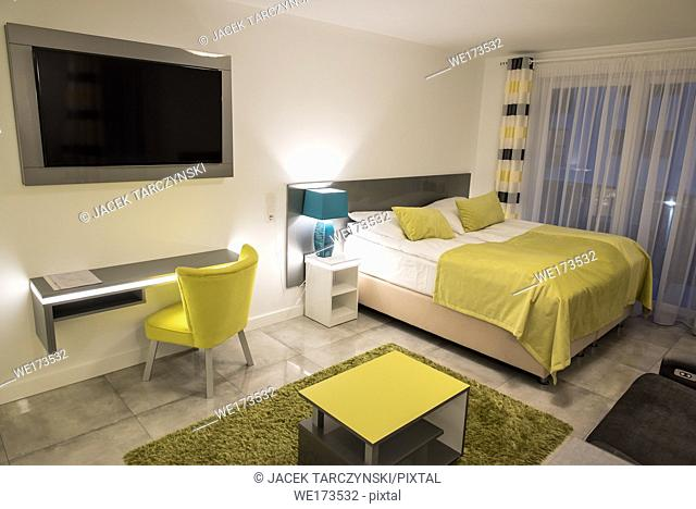Comfortable bedroom in modern apartment in yellow green colour tone