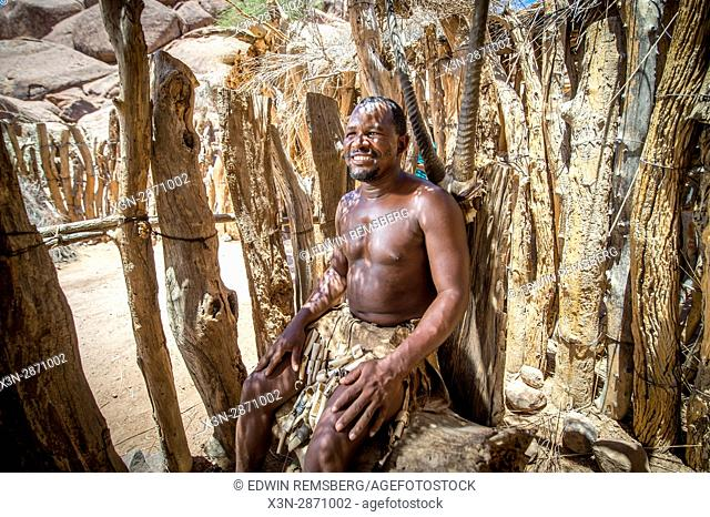 A Damara man dressed in traditional clothing smiles for a photograph at the Damara Living Museum in Twyfelfontein, located in the southern region of Namibia