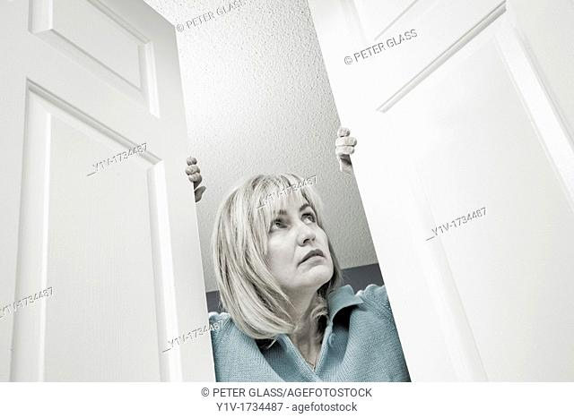Middle-age blond woman looking out through double doors