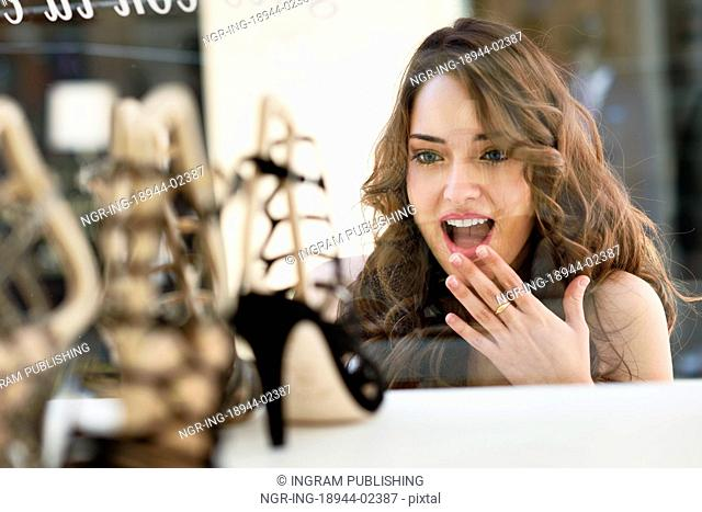 Woman looking to showcase or shop window. Shopping girl chooses shoes in store
