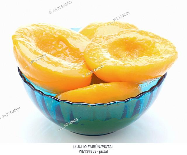 Cut peaches in syrup in blue bowl isolated on white