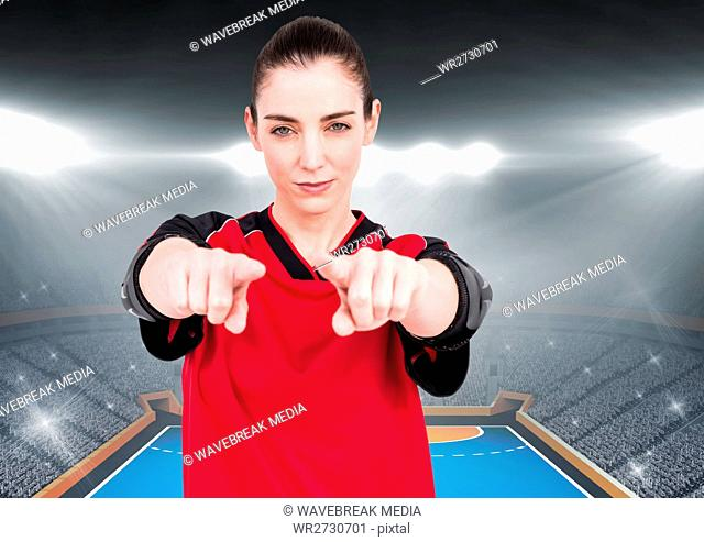 Confident female athlete gesturing against stadium background