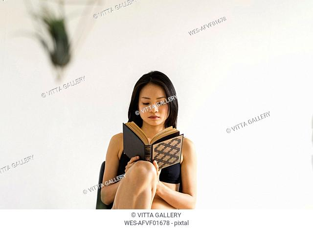 Attractive young woman in lingerie sitting on chair at home reading book