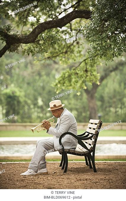 Senior African man playing trumpet on bench in park